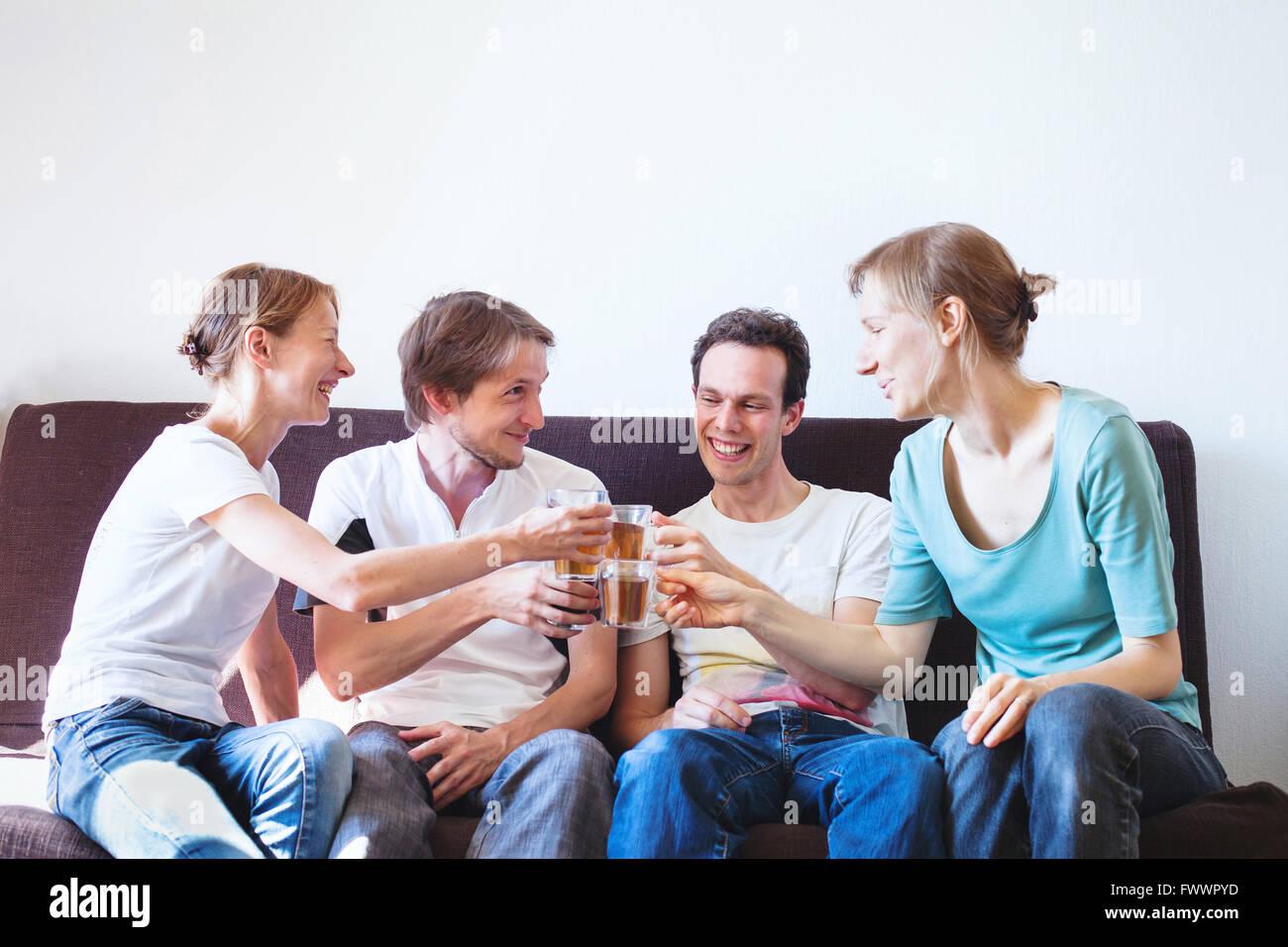 Gruppo di amici il tifo a casa felice giovane popolo sorridente con bevande, copyspace Immagini Stock