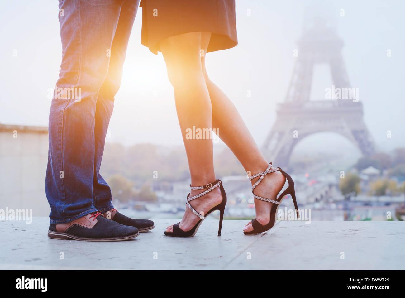 Una vacanza romantica a Parigi, i piedi del giovane kissing vicino a Torre Eiffel Immagini Stock