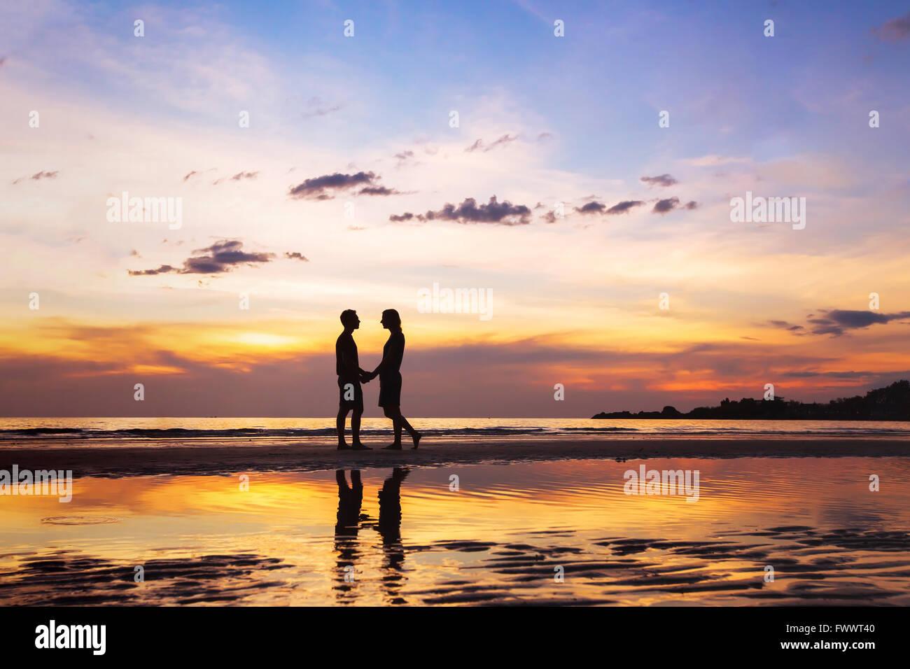 Silhouette di affettuosa giovane sulla spiaggia al tramonto, amore concetto, uomo e donna, bello sfondo Immagini Stock