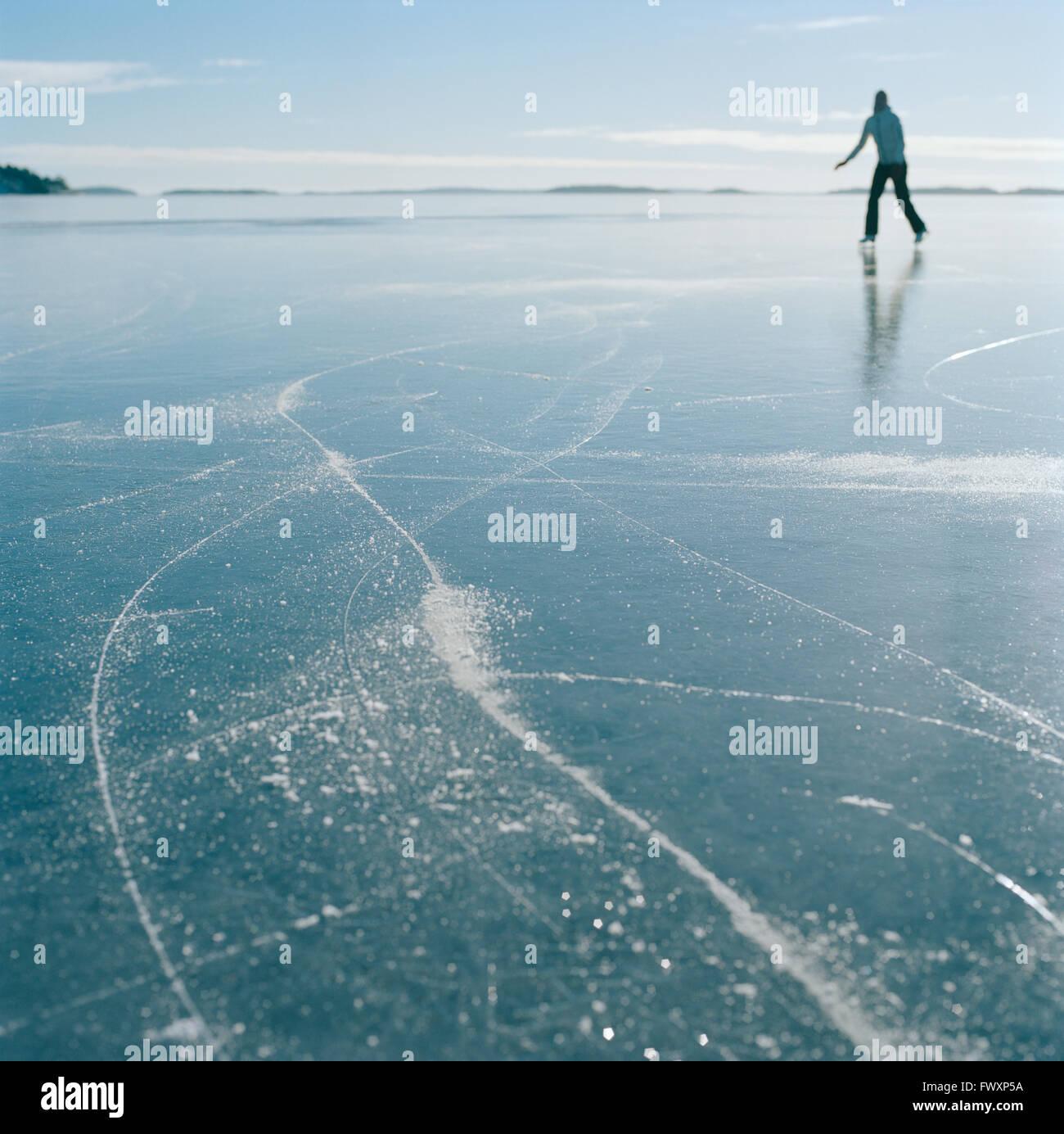 La Svezia, arcipelago di Stoccolma, Uppland, Varmdo, Bjorno, metà donna adulta pattinaggio sul lago ghiacciato Immagini Stock