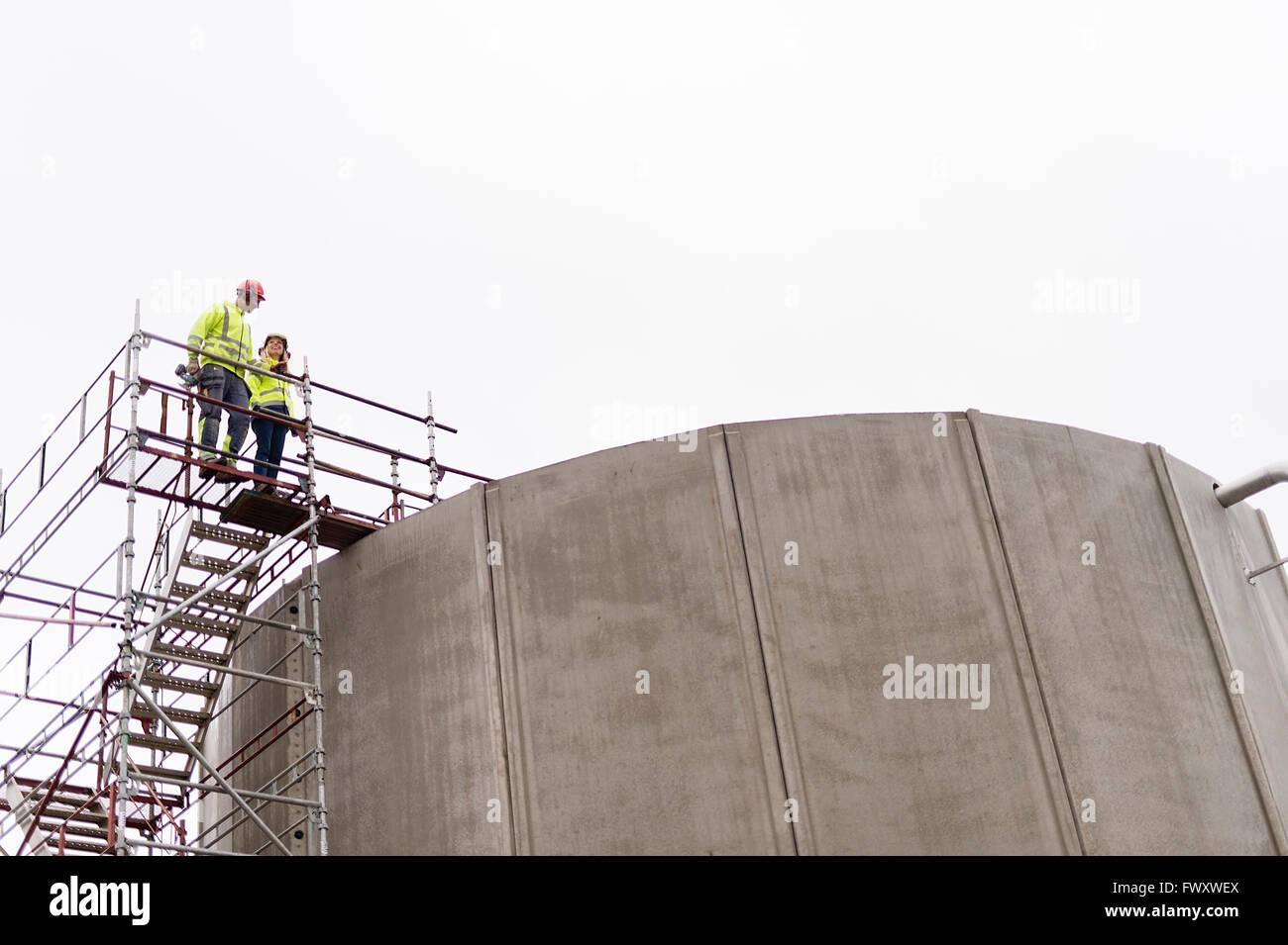La Svezia, Vastmanland, l uomo e la donna in piedi su un ponteggio da impianto di trattamento delle acque Immagini Stock