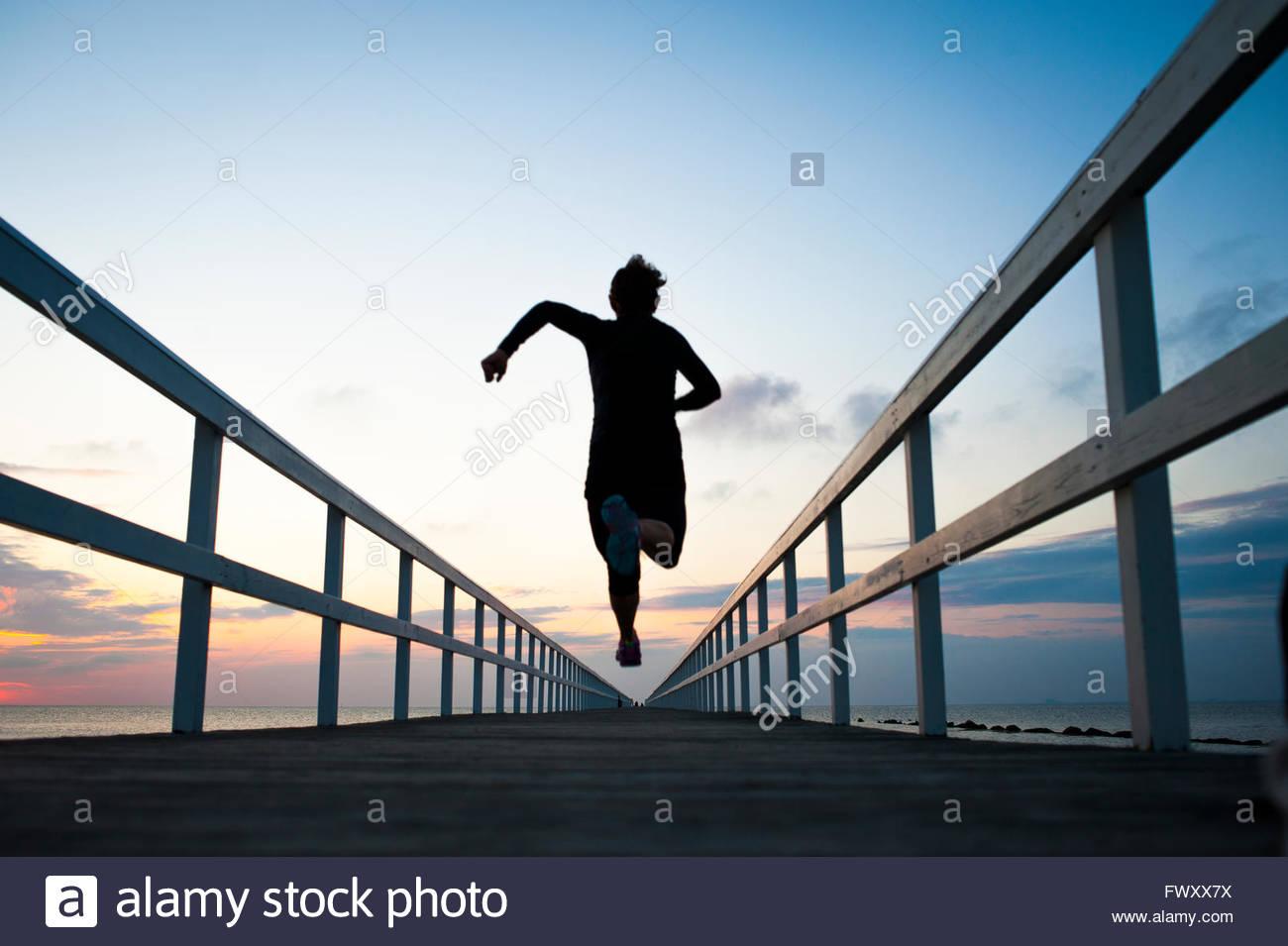 La Svezia, Skane, Malmo, giovane donna in esecuzione sul molo al tramonto Immagini Stock