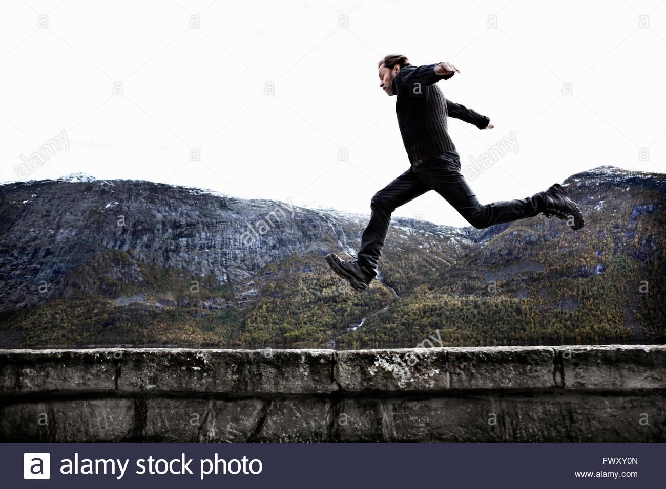 Norvegia Odda, uomo saltando su muro di pietra Immagini Stock