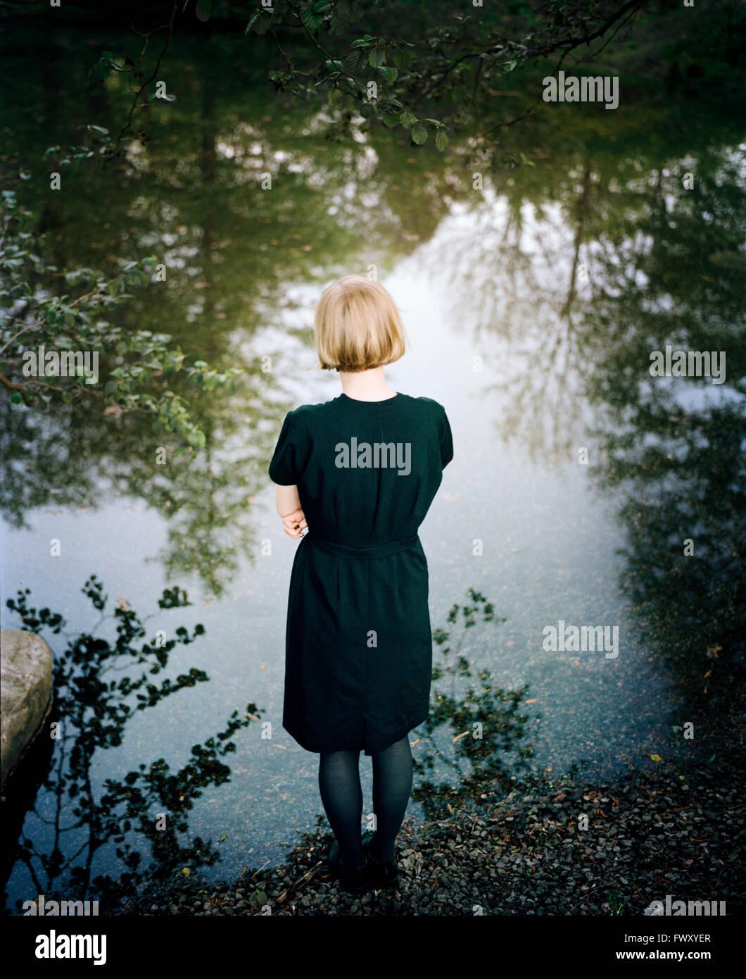 Finlandia, Varsinais-Suomi, giovane donna in piedi sul bordo del lago Immagini Stock