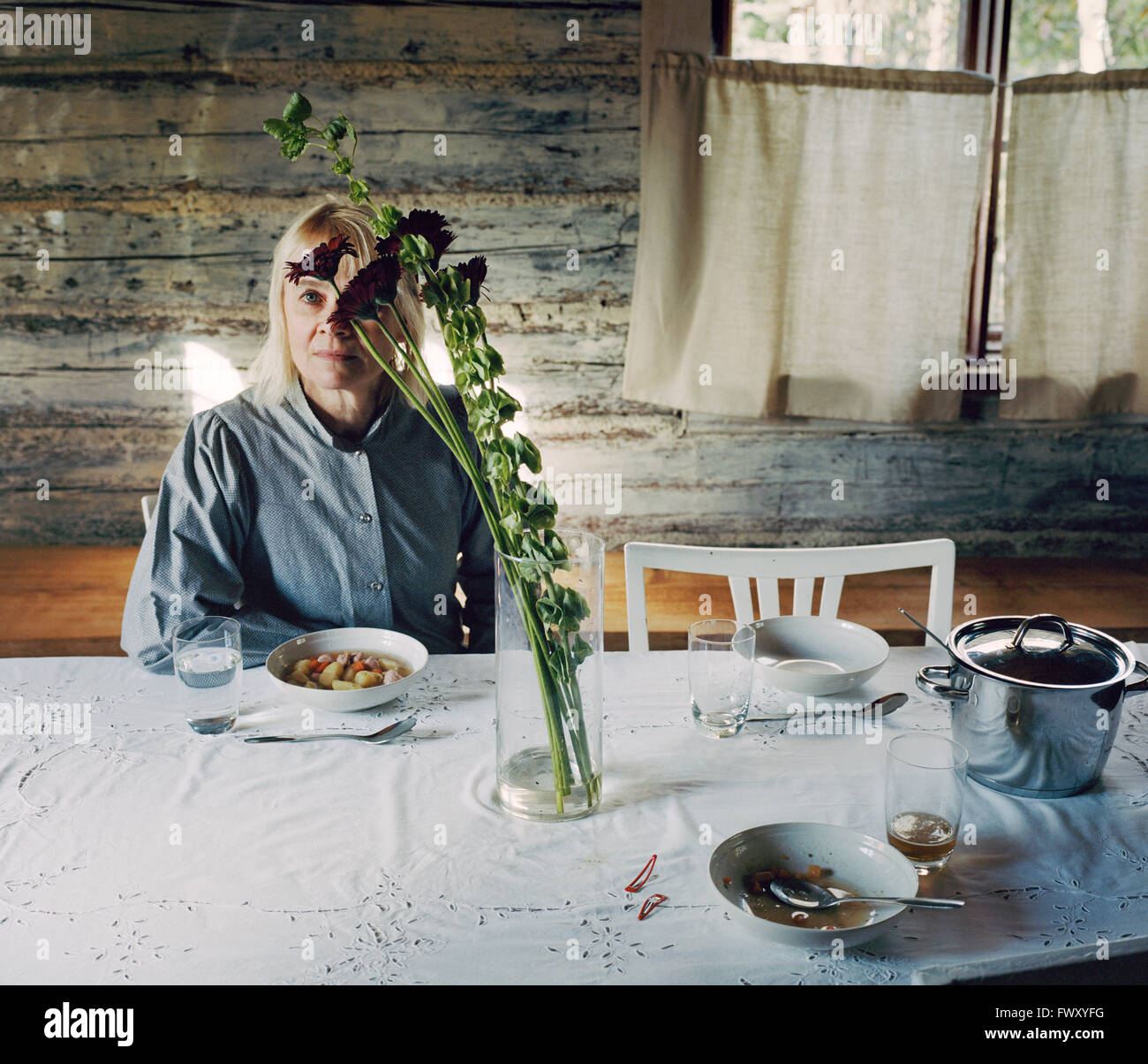 Finlandia, donna matura seduta a tavola Immagini Stock