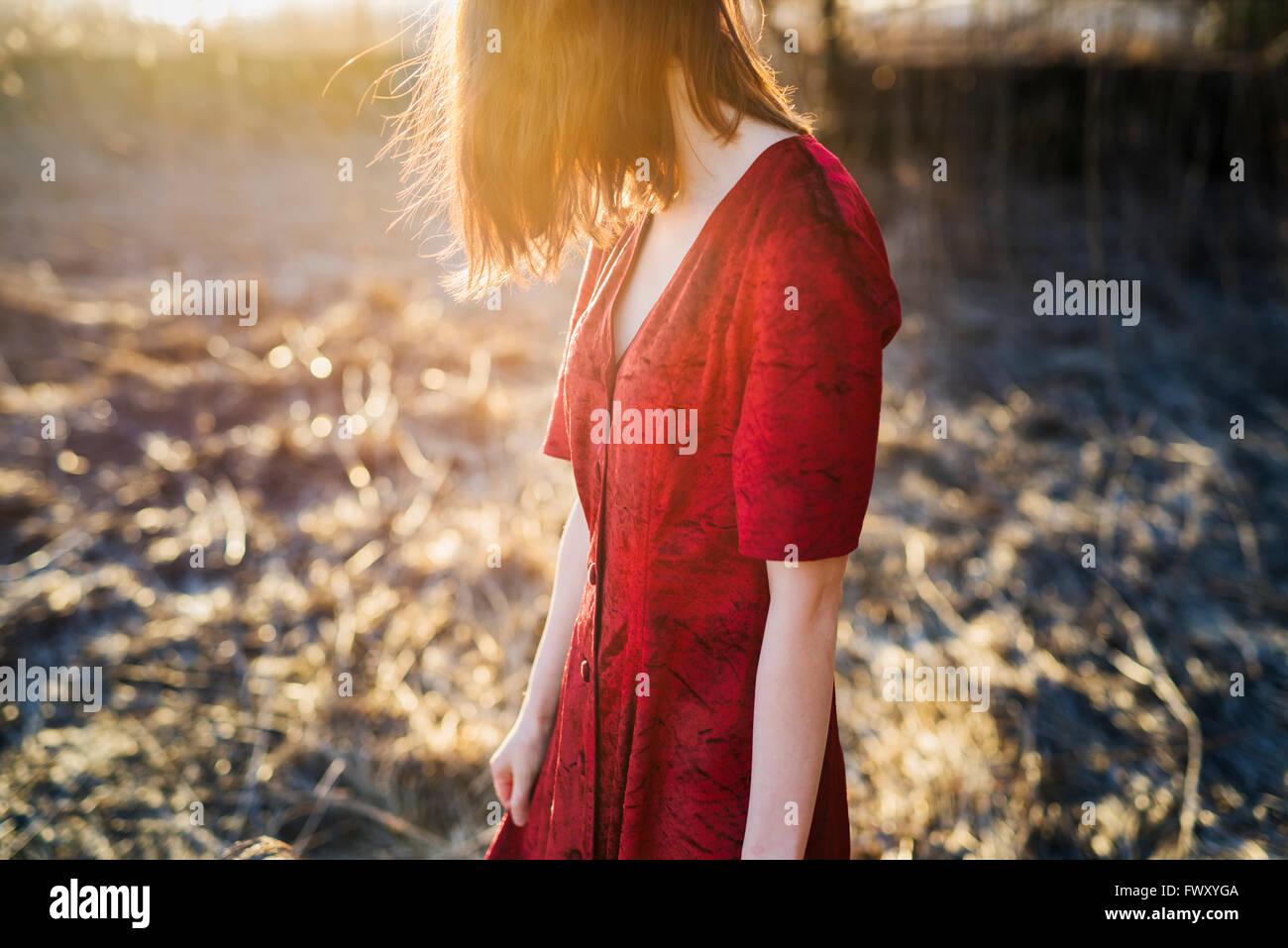 Finlandia, Varsinais-Suomi, rosso giovane donna capelli in abito rosso in piedi nella luce solare Immagini Stock