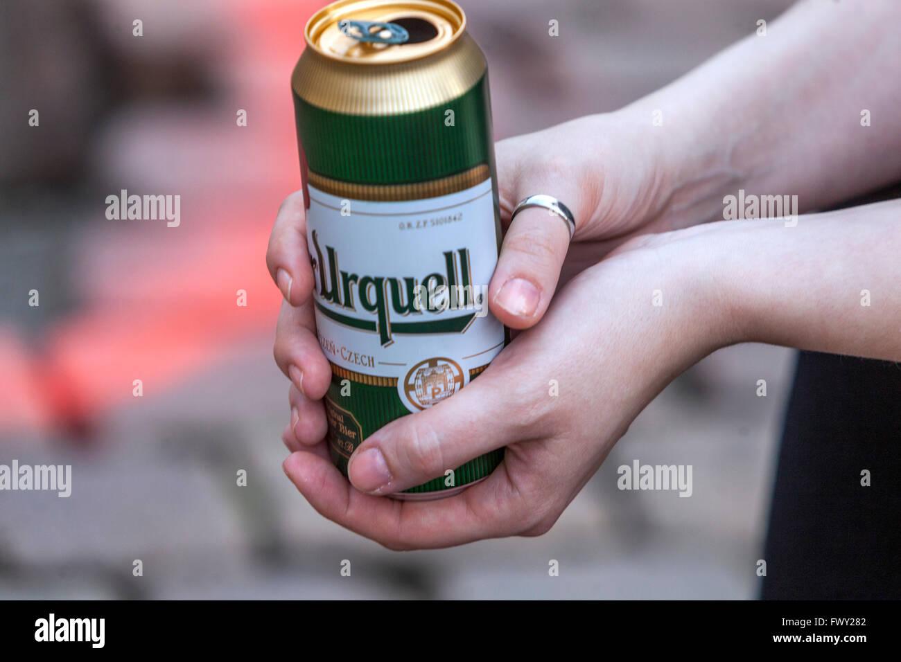 La donna è in possesso di una lattina di birra Pilsner Urquell Immagini Stock
