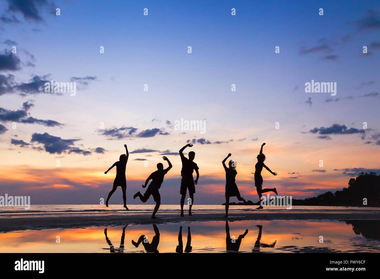 Gruppo di persone che saltano sulla spiaggia al tramonto, silhouette di amici divertendosi insieme Foto Stock