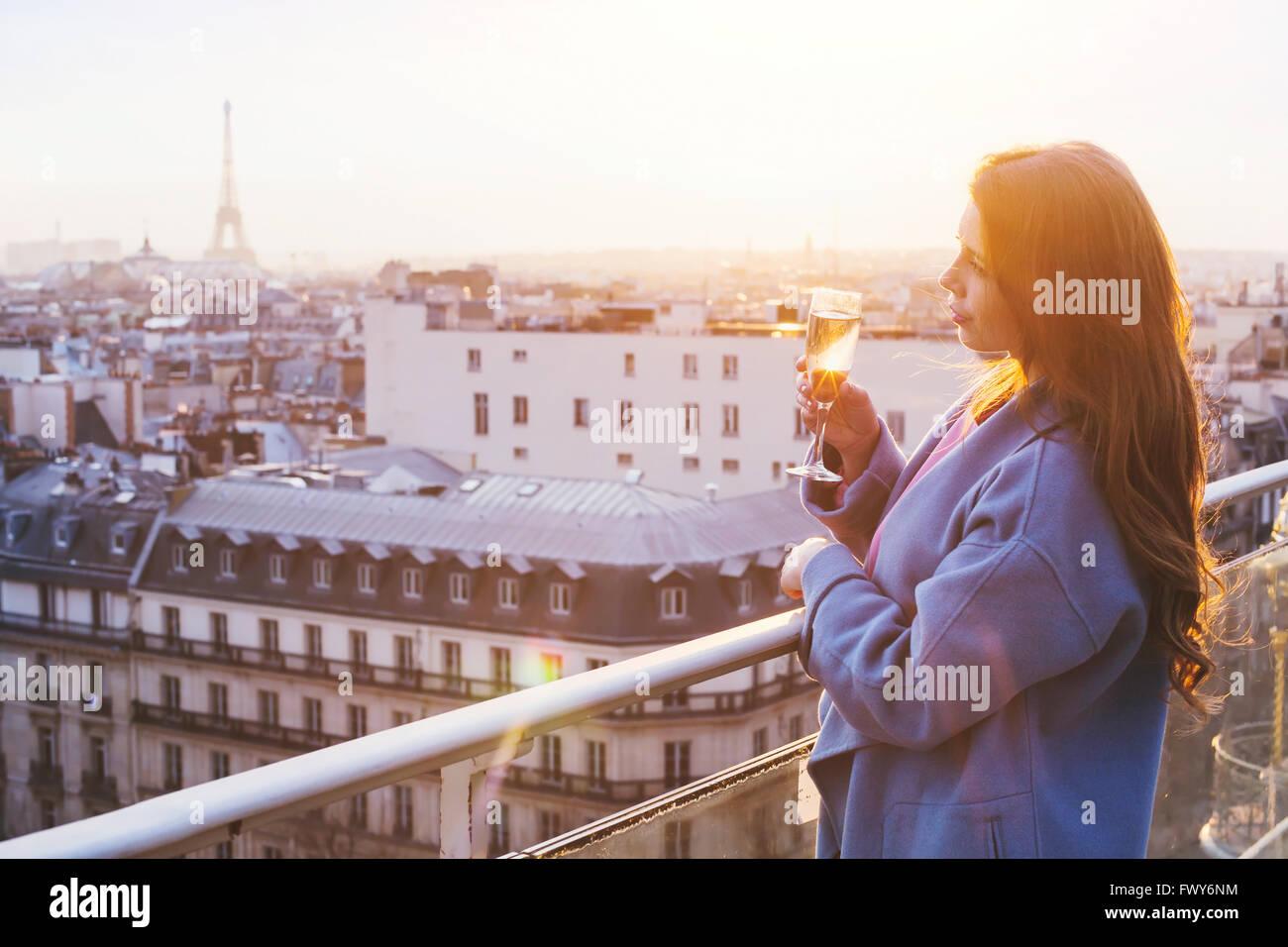 Donna godendo di una vista panoramica di Parigi e la Torre Eiffel al tramonto, tenendo in mano un bicchiere di vino Immagini Stock