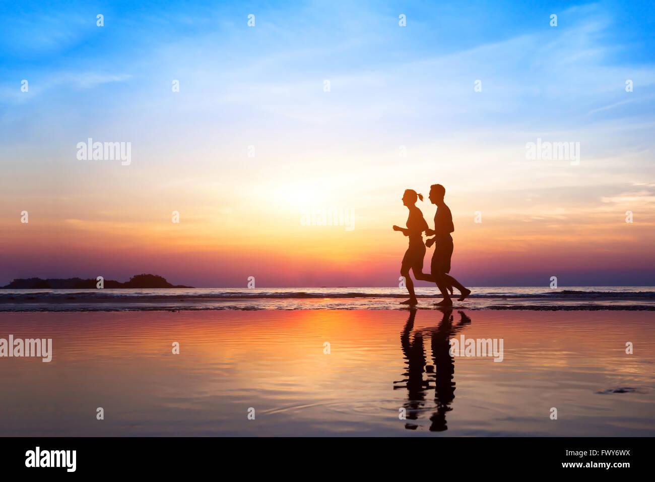Sfondo di allenamento, due persone jogging sulla spiaggia al tramonto, corridori sagome, uno stile di vita sano Immagini Stock