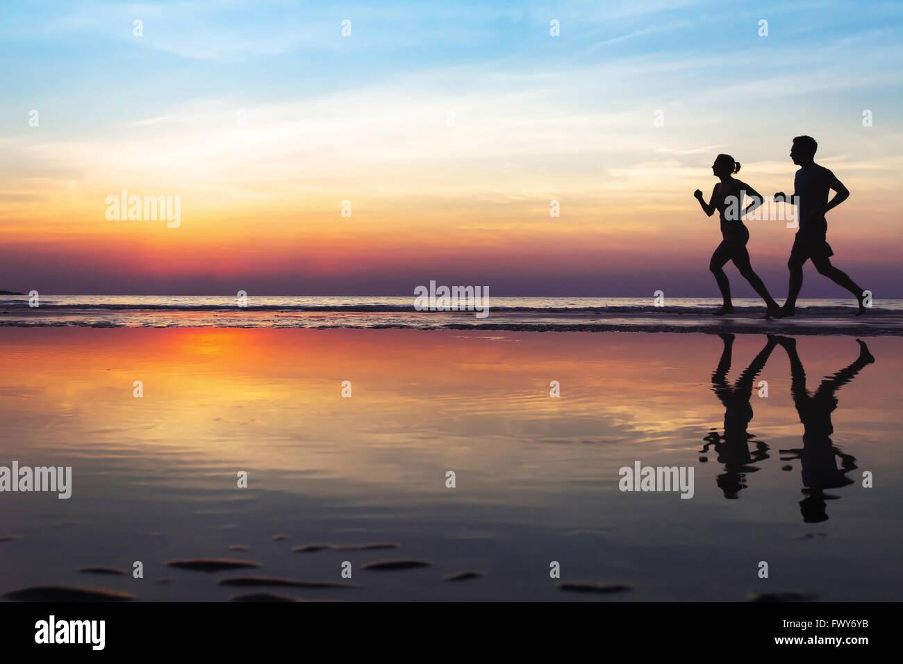 Due guide di scorrimento sulla spiaggia, silhouette di persone jogging al tramonto, uno stile di vita sano sfondo Immagini Stock
