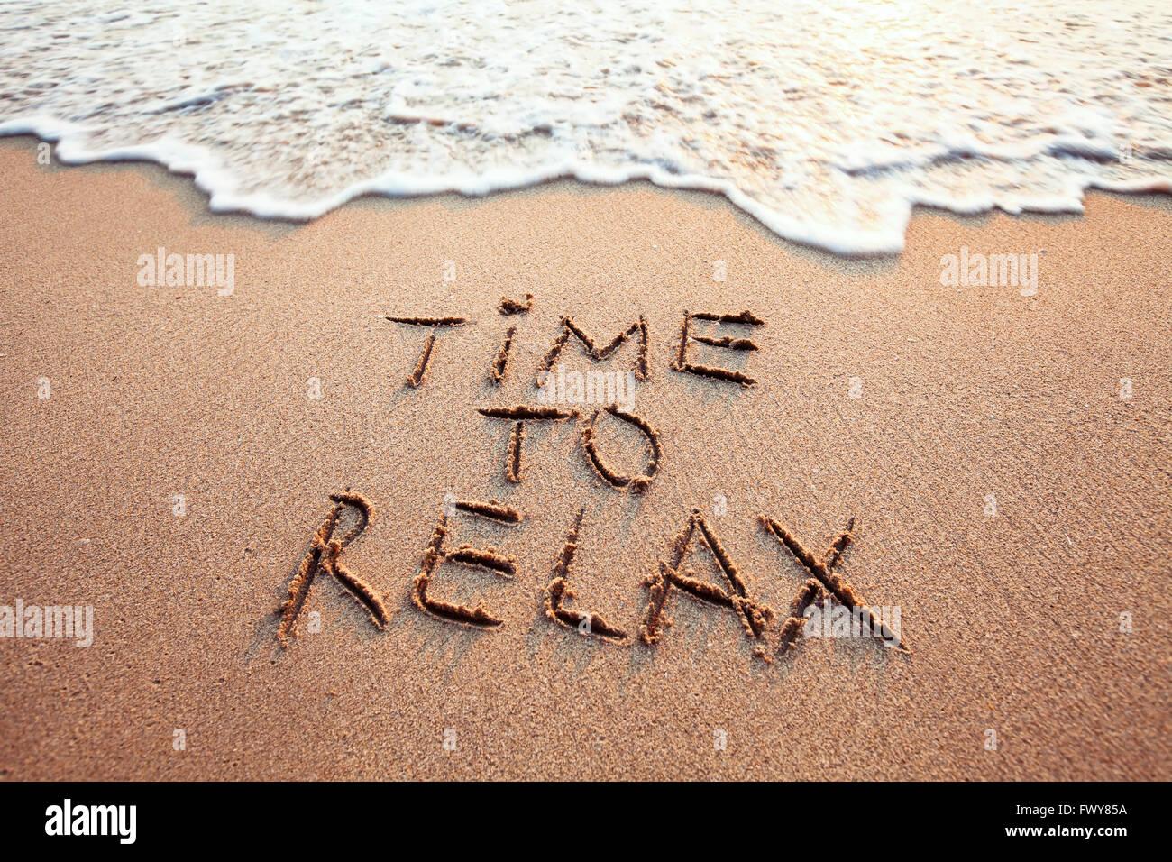 Tempo di rilassarsi, concetto scritta sulla spiaggia sabbiosa Immagini Stock