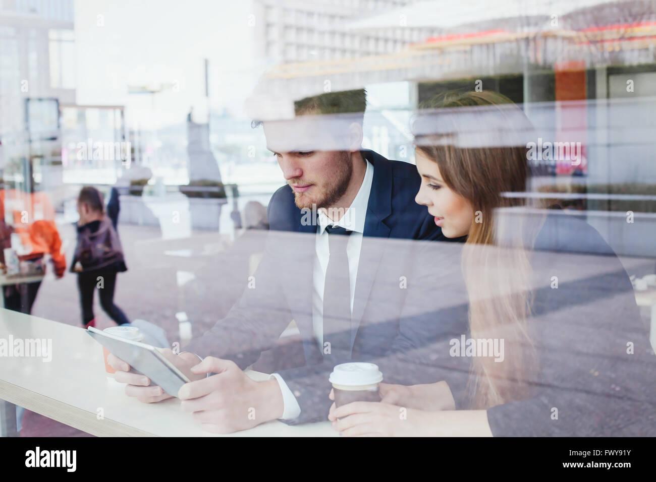 La gente di affari in cafe guardando lo schermo del tablet Immagini Stock