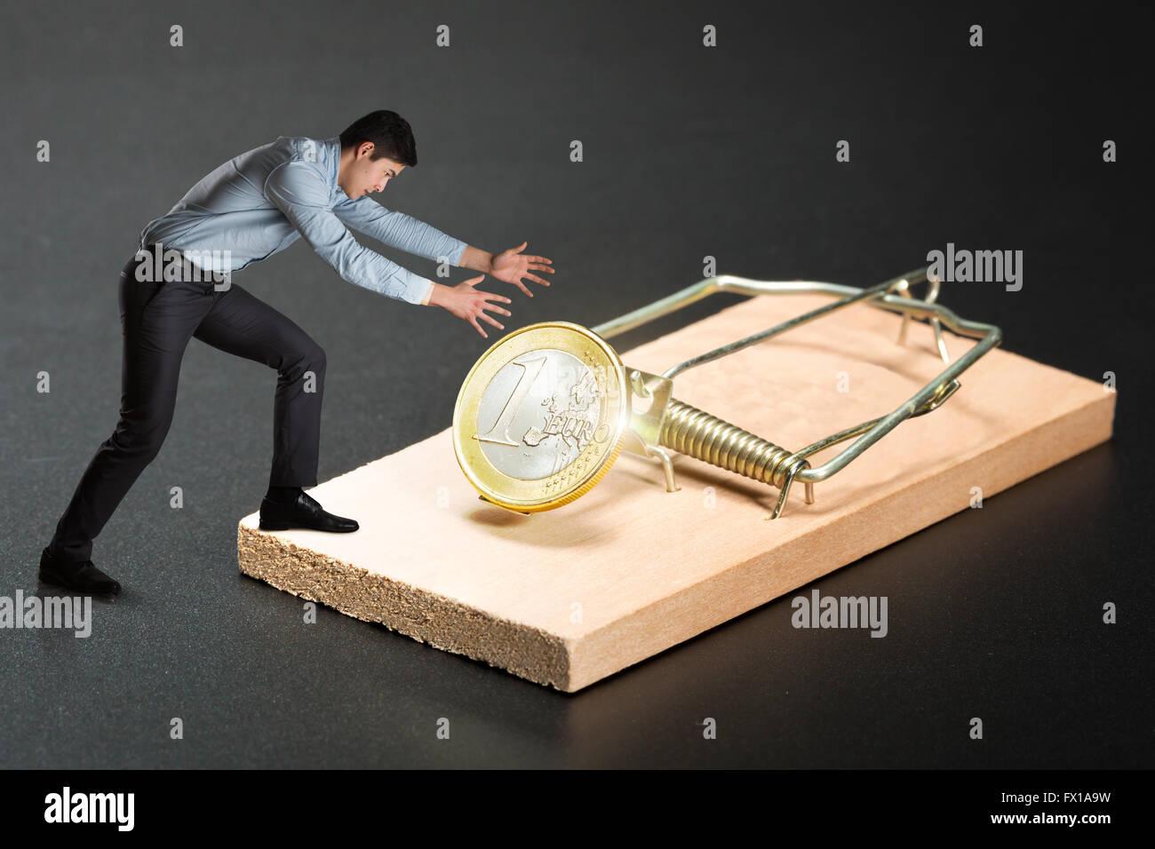 Uomo che cerca di scegliere una moneta in oro Immagini Stock