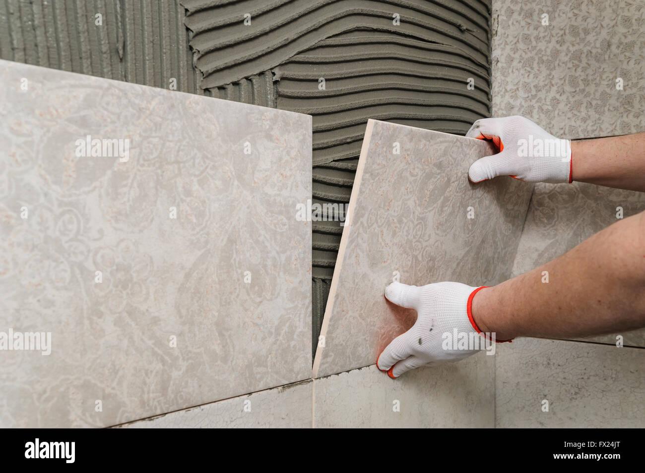 La posa di piastrelle in ceramica installatore mette piastrella