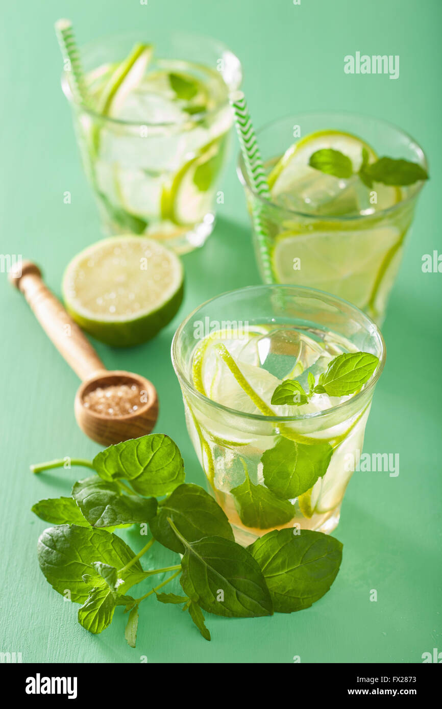 Cocktail mojito e ingredienti su sfondo verde Immagini Stock