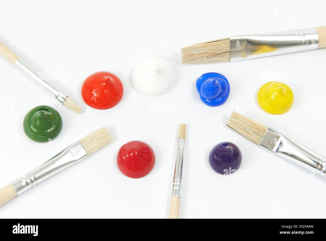 Colori acrilici e pennelli su sfondo bianco Immagini Stock