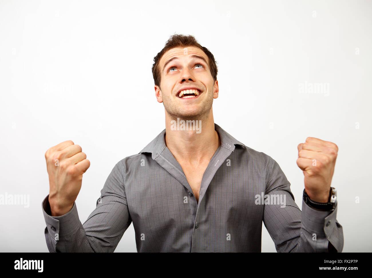Entusiasta vincitore maschio che esprimono la vittoria e il successo. Business di successo uomo isolato su grigio Immagini Stock