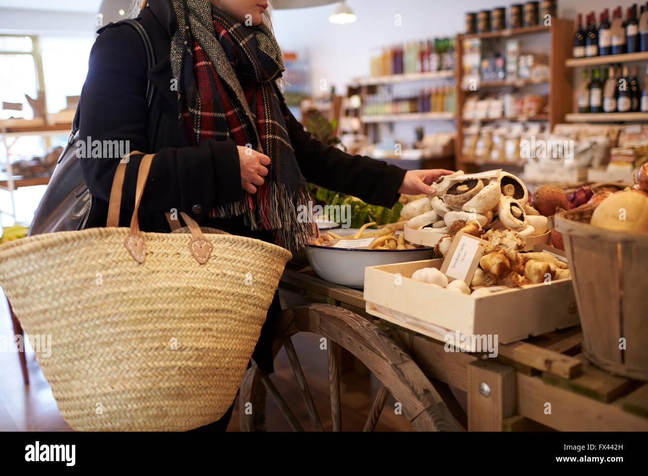 Close up della Donna Shopping per produrre nel negozio di specialità gastronomiche Immagini Stock