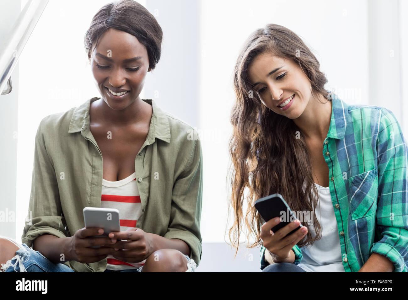 Gli amici utilizzando il telefono cellulare Immagini Stock