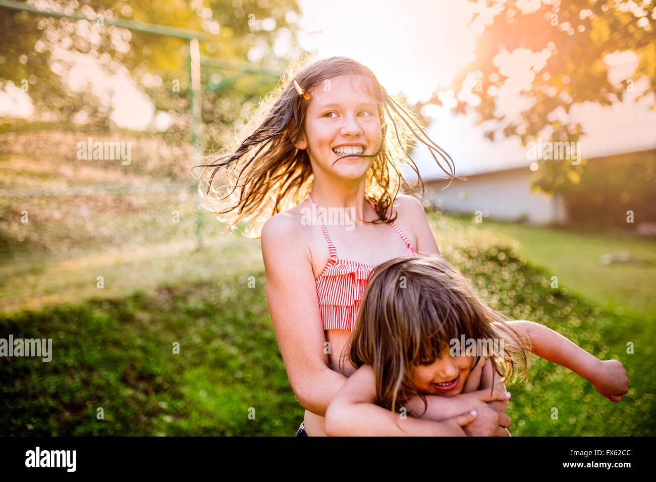Due cute ragazze avendo divertimento fuori nel giardino estivo Immagini Stock