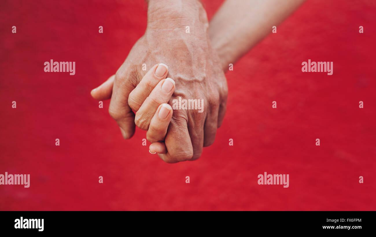 Close up di un uomo e di una donna tenendo le mani contro lo sfondo di colore rosso. Affettuosa giovane tenendo Immagini Stock