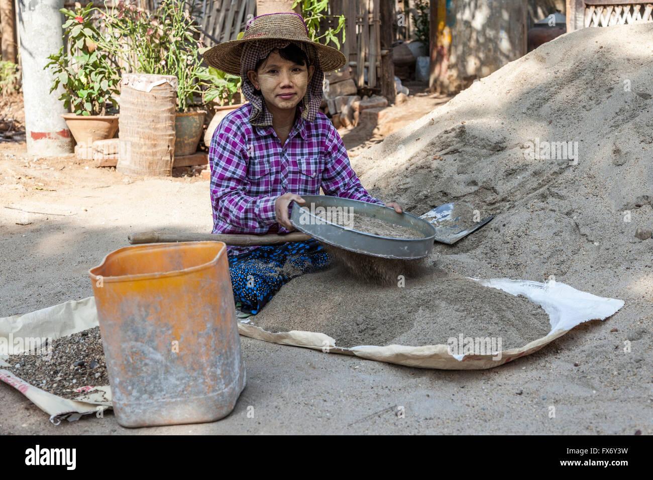 A New Bagan, un apprendista giovane donna preparare la malta per operai su un sito di costruzione (Myanmar). Immagini Stock