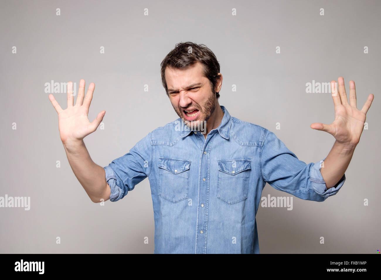 L'uomo arrabbiato su sfondo grigio isolato Immagini Stock