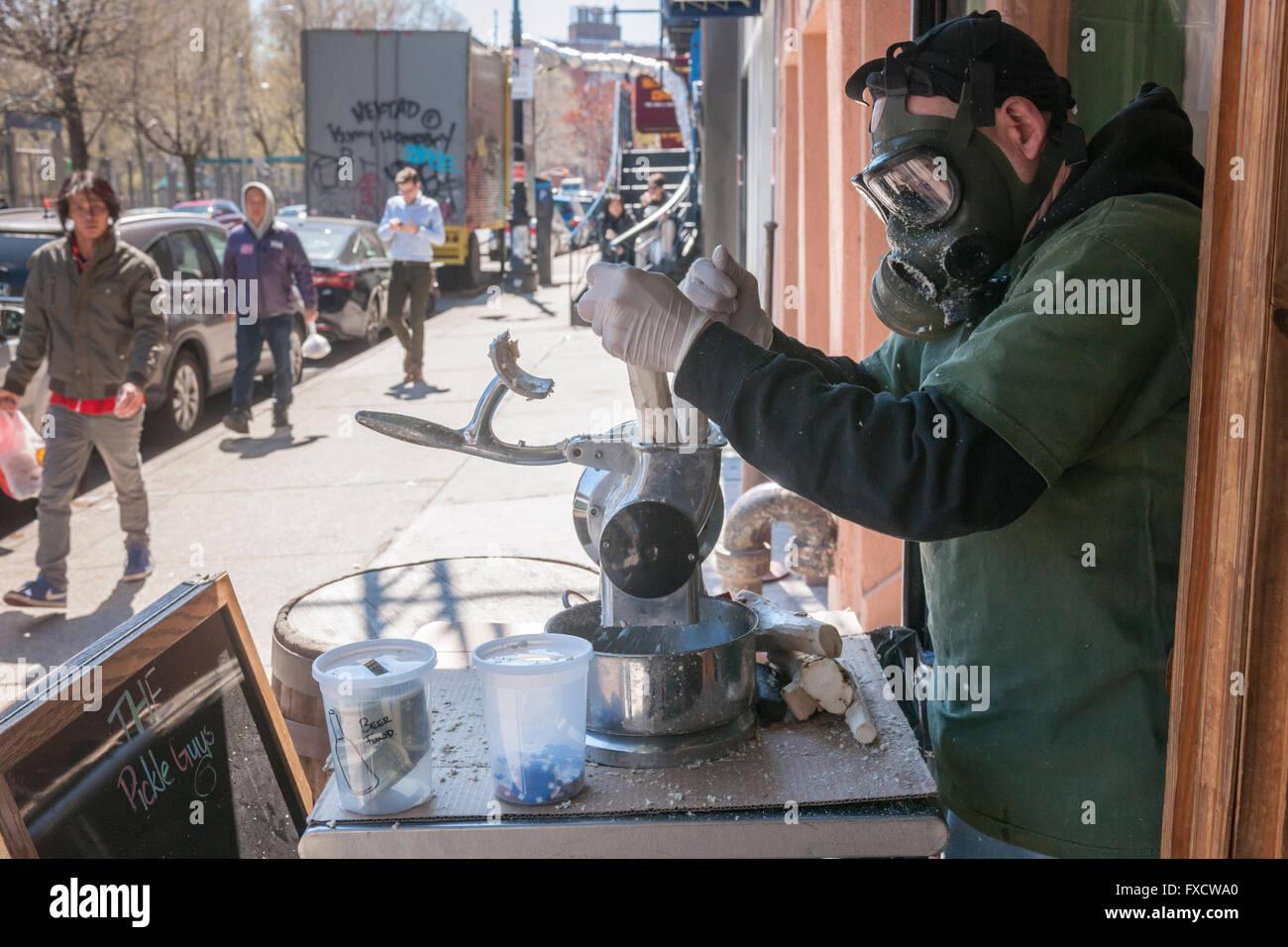 Un lavoratore di indossare un respiratore di grind il rafano per la salamoia ragazzi store nel Lower East Side di Immagini Stock