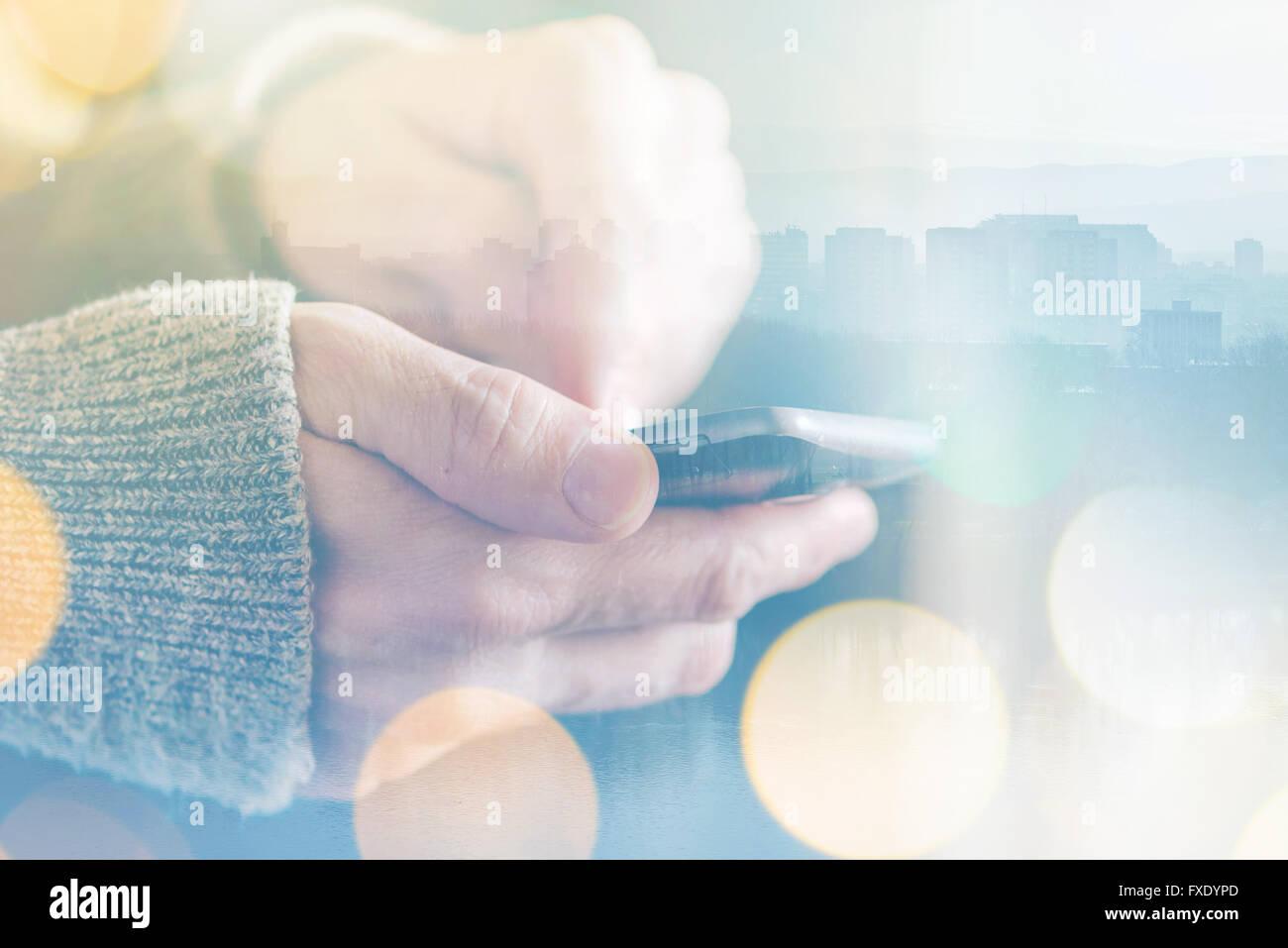 Uomo di inviare un messaggio di testo sullo smartphone, la luce del sole di mattina attraverso la finestra, maschio Immagini Stock