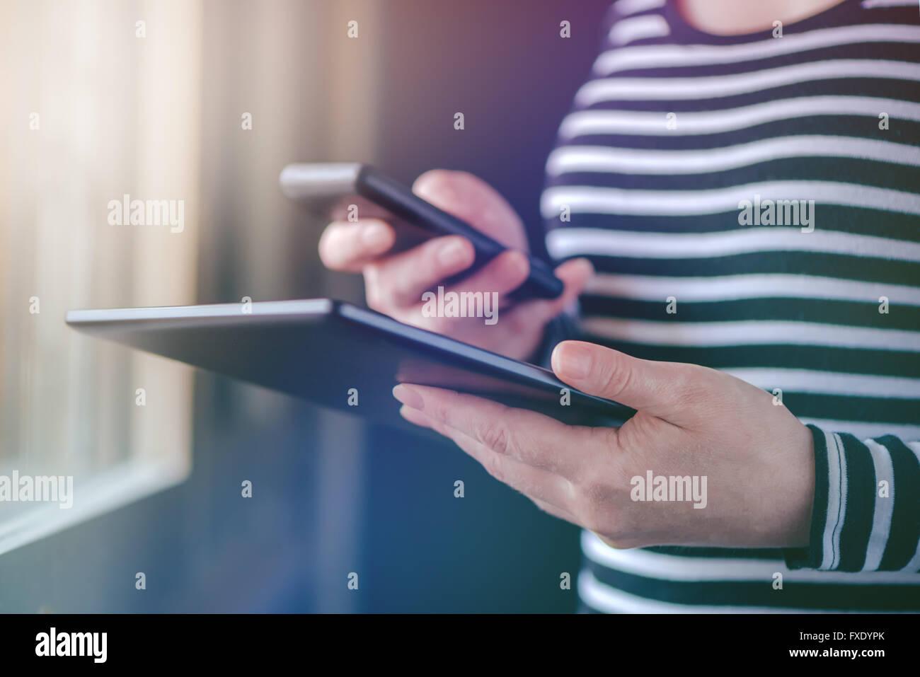 Smartphone e Tablet la sincronizzazione dei dati, la donna la sincronizzazione di file e documenti su personal wireless Immagini Stock