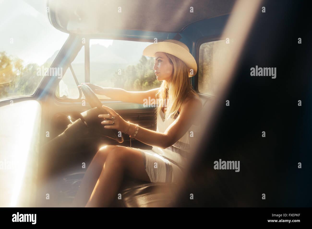 Ritratto di giovane e bella donna che indossa un cappello alla guida di una vettura sulla giornata di sole. Giovane Immagini Stock