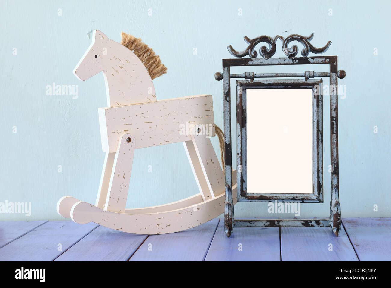 Bianco antico in stile vintage telaio e il vecchio cavallo a dondolo su un tavolo di legno. Immagini Stock