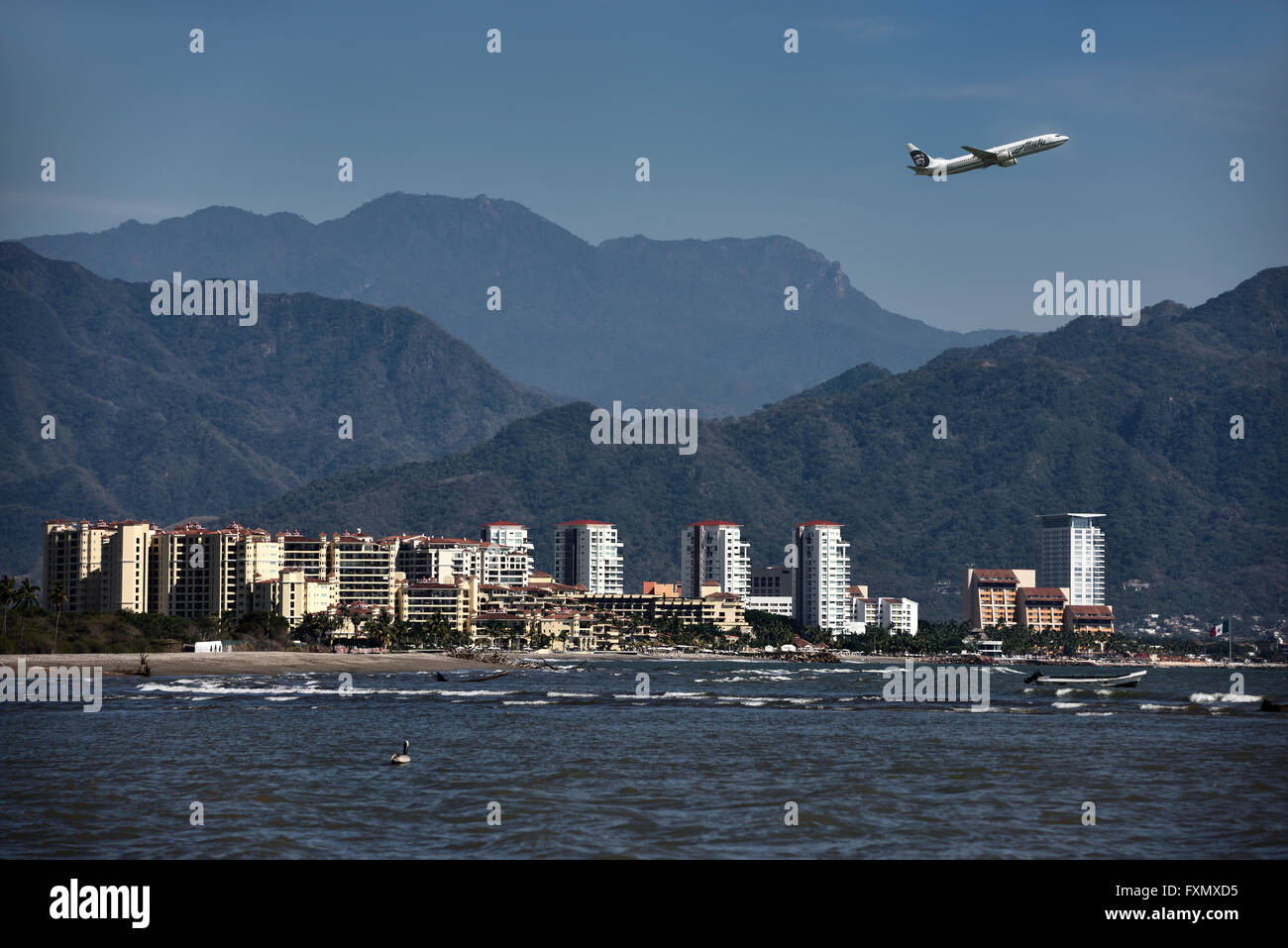 Piano di getto di decollare da Puerto Vallarta aeroporto con oceano Pacifico e Sierra Madre mountains Immagini Stock