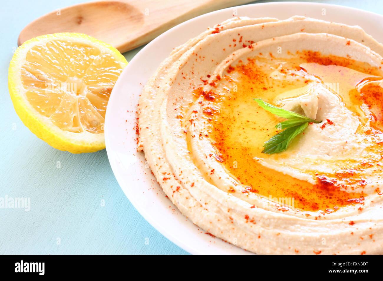 Hummus immergere la piastra sul tavolo di legno Immagini Stock