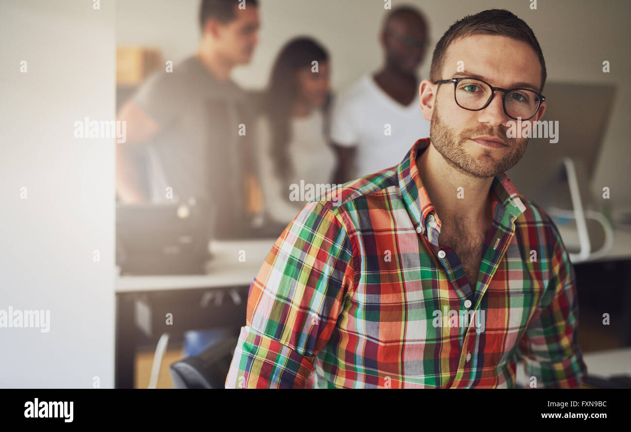 Grave maschio singolo proprietario di affari indossando variopinti pulsante di flanella camicia con tre lavoratori Immagini Stock