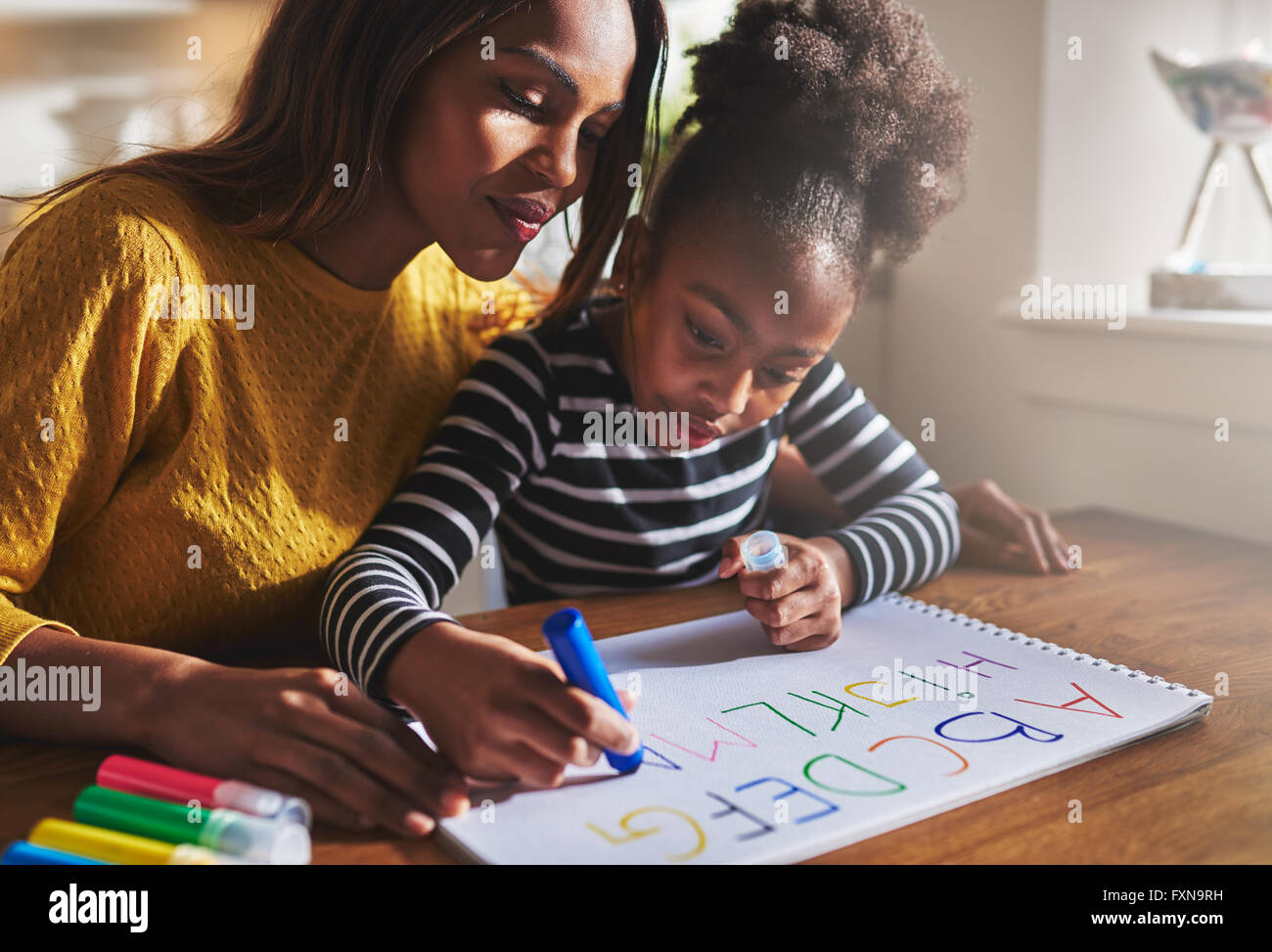 Bambina iscritto l'alfabeto con la madre a casa Immagini Stock