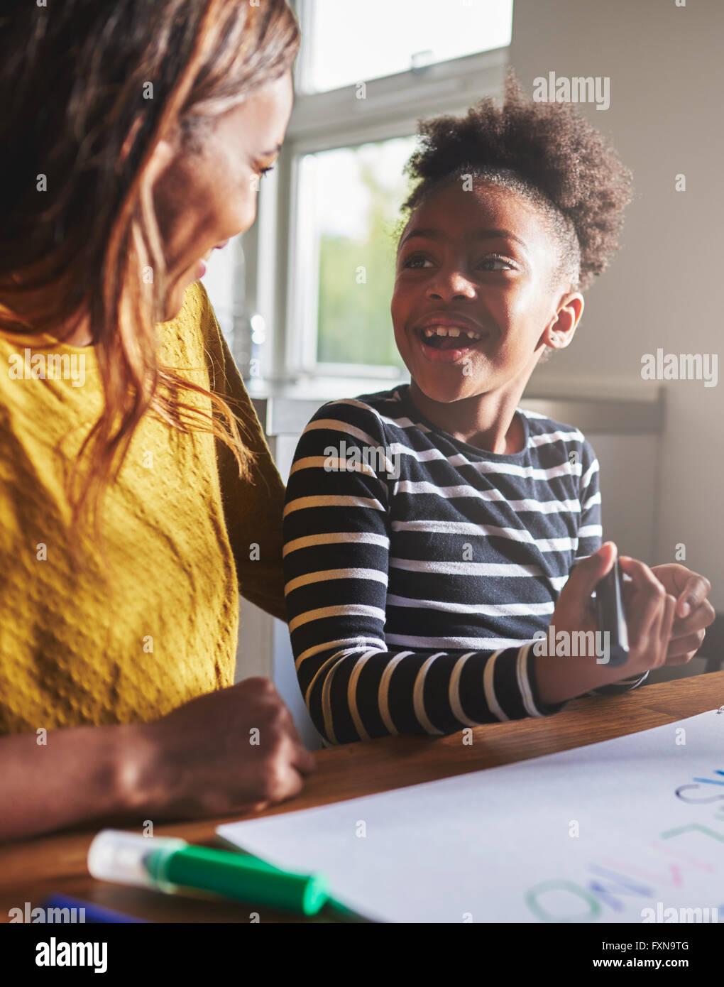 Bambino felice imparare l'alfabeto con sua madre, nero donna e bambino Immagini Stock