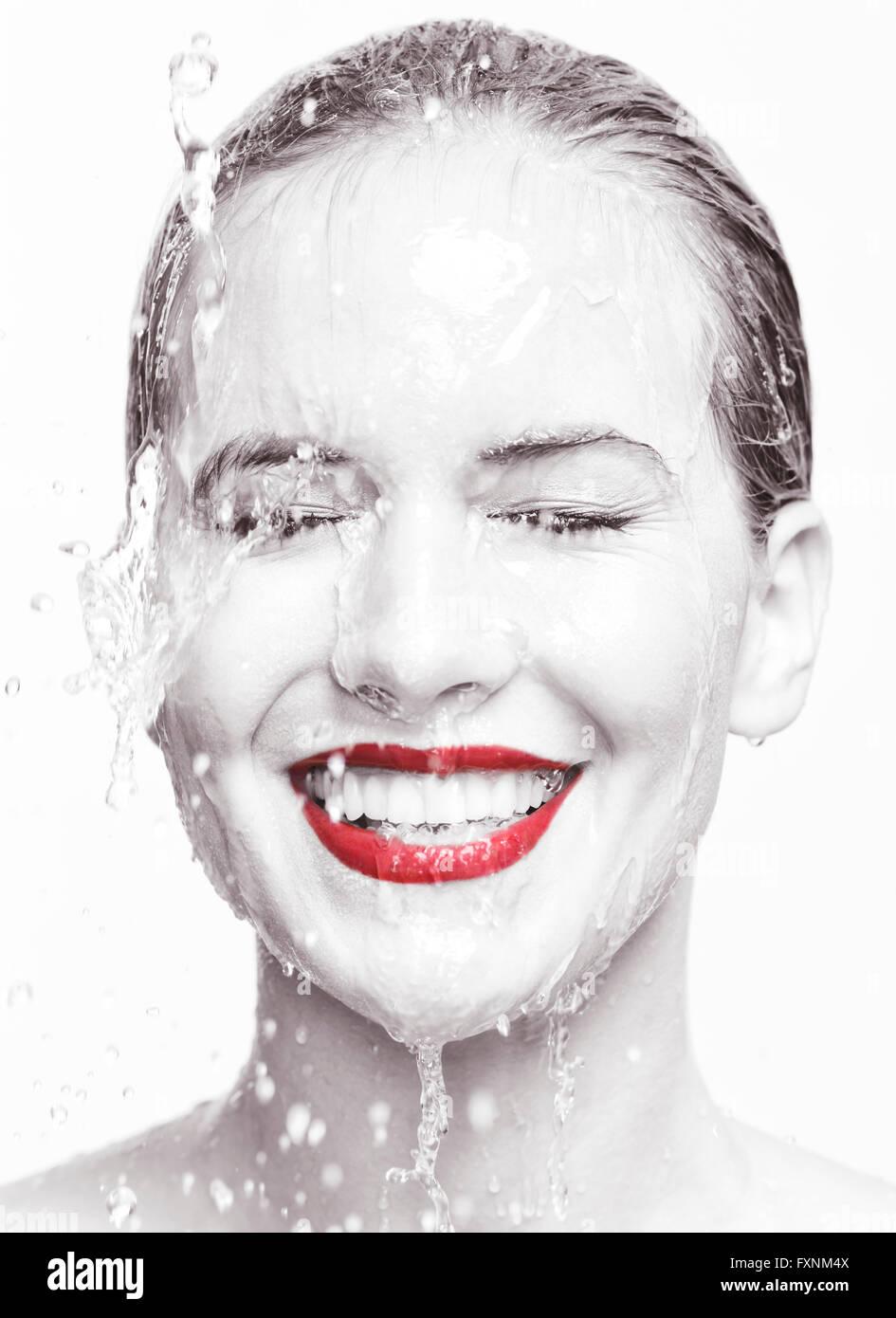 Sorridente volto di donna con rossetto rosso con acqua in esecuzione su di esso Immagini Stock