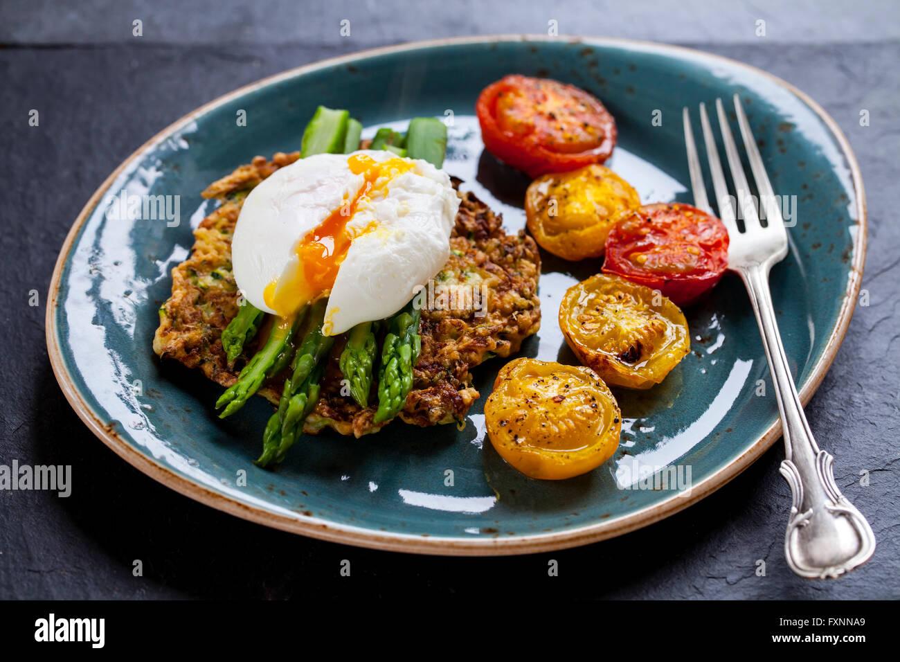 La zucchina röstinchen, Uovo affogato, asparagi e pomodori arrosto Immagini Stock