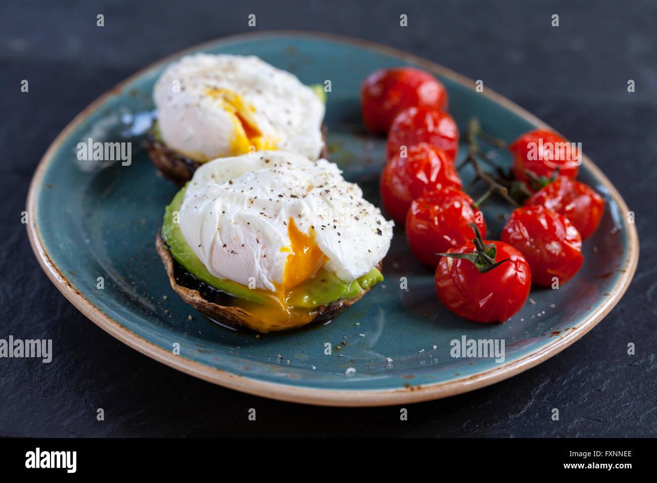 La colazione, i funghi con avocado e uova in camicia e arrostire i pomodori ciliegia sulla vite Immagini Stock
