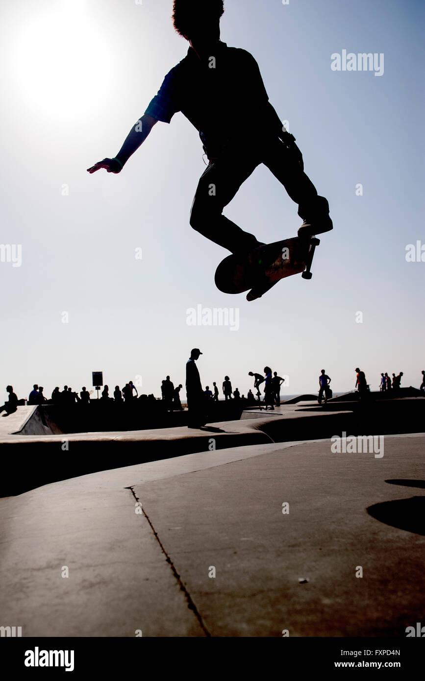 Guidatore di skateboard in midair a skate park Immagini Stock