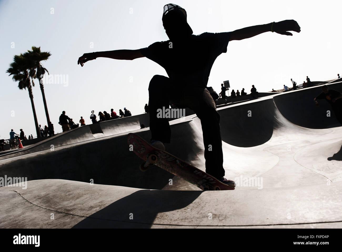 Giovane uomo skateboarding in skate park Foto Stock
