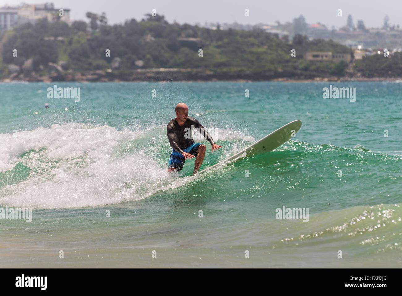 L'uomo surf un ondata di Manly Beach, cerca di mantenere l'equilibrio. A sette miglia dal centro di Sydney, Immagini Stock