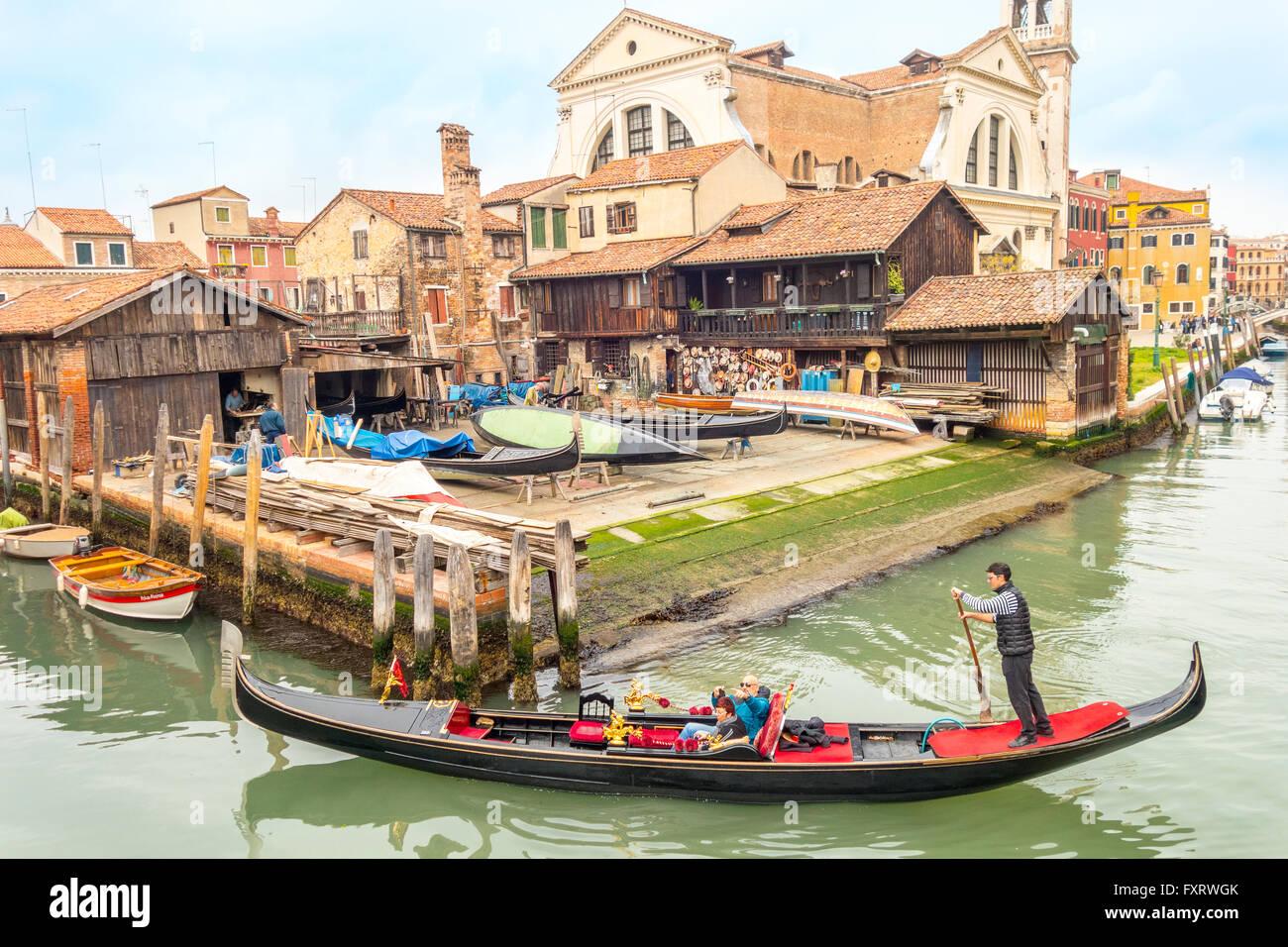 Venezia Italia. Gondola Veneziana sul Rio San Trovaso passando la gondola workshop cantiere Squero di San Trovaso nel sestiere di Dorsoduro Foto Stock