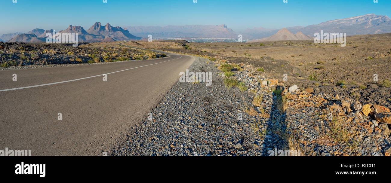 Autostrada attraverso deserto ruvido in Al Hajar mountain range, Oman. Immagini Stock
