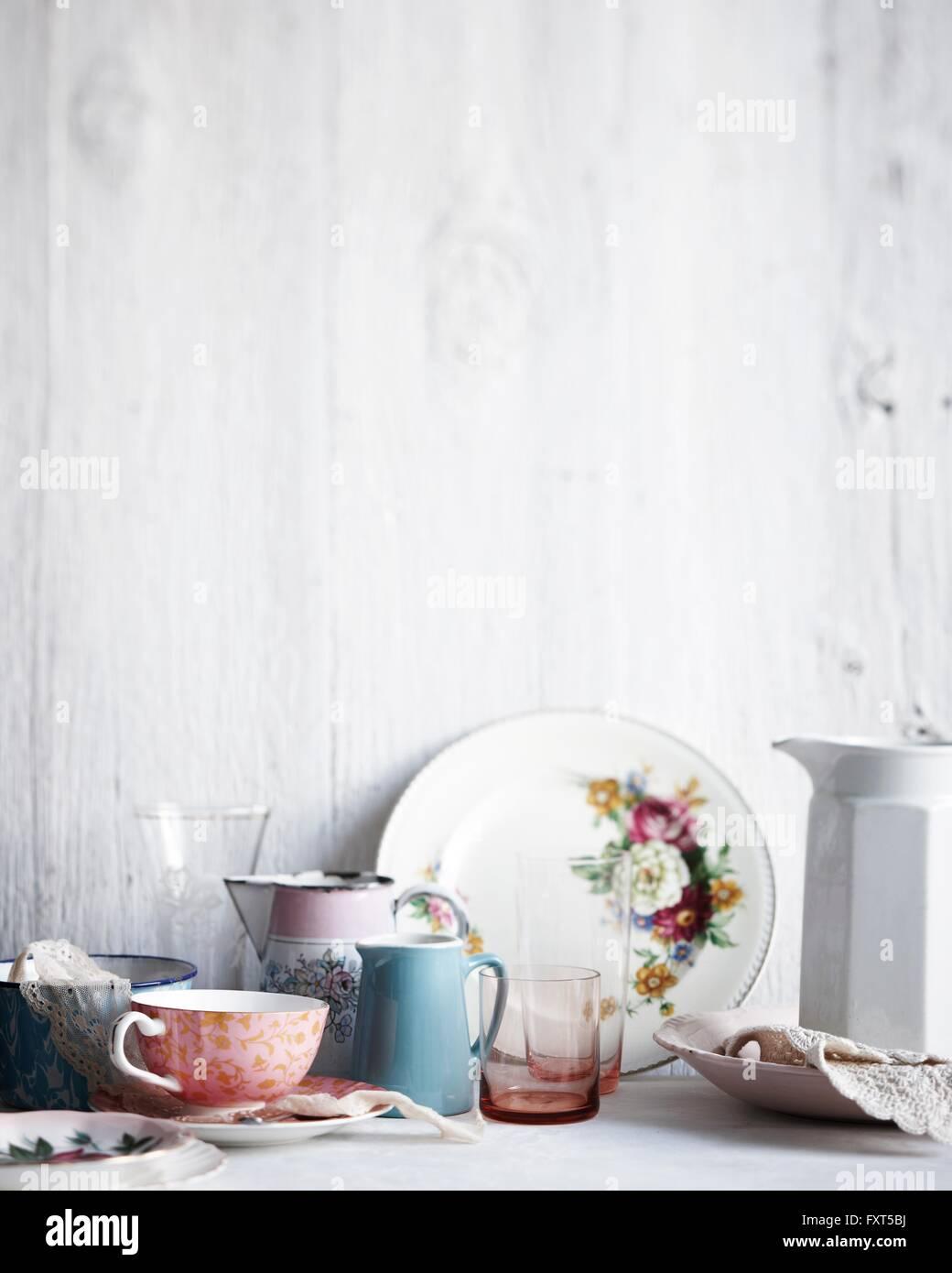 Varietà di bicchieri, piatti e brocche sulla tavola dipinta di bianco Immagini Stock