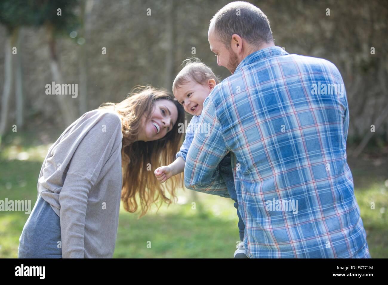 I genitori tenendo sorridente baby boy, riproduzione Immagini Stock
