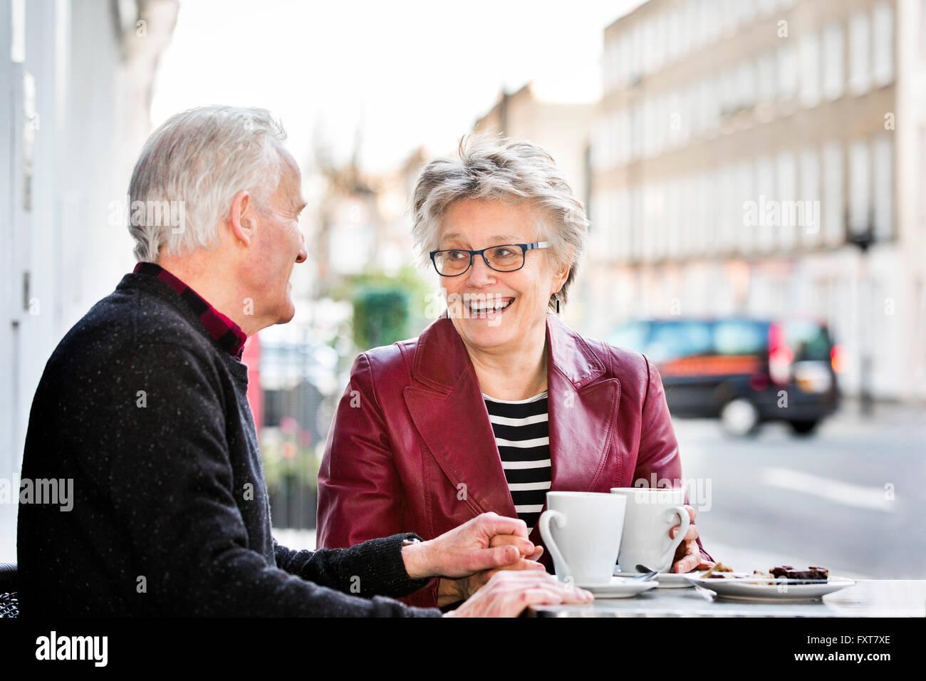 Romantico coppia senior presso cafè sul marciapiede tenendo le mani Immagini Stock