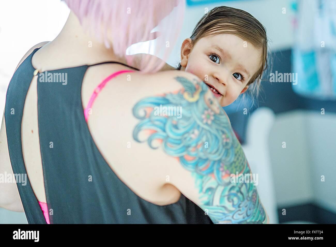 Ritratto di baby boy peeking oltre il suo madri tattoed spallamento Immagini Stock